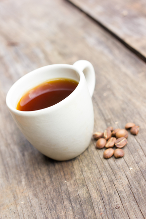buccal: Coffee cup with roasted coffee beans on wooden background. Stock Photo