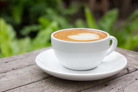coffee latte art in coffee shop , on wood table.