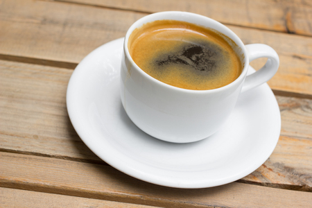 Cup of hot coffee on a wooden table in cafe. Stock Photo
