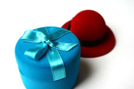 Two boxes for gifts in the form of a red hat and a blue round box photo