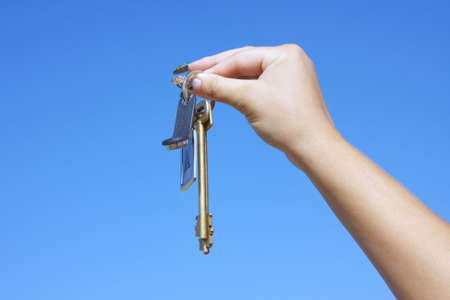 copula: woman hand with the keys on a background sky