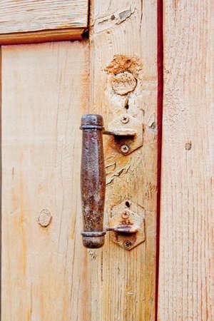 rusty handle on an old wooden door handle
