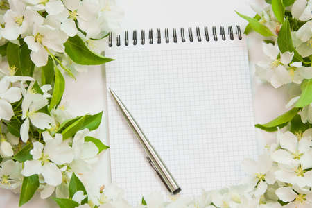 beautiful designer background with the sprigs of flowering apple-tree with a notebook and pen