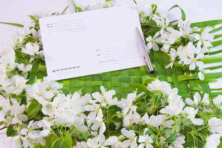 beautiful designer background with the sprigs of flowering apple-tree with an envelope and pen