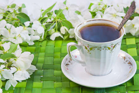cup of coffee with the sprigs of flowering apple-tree photo