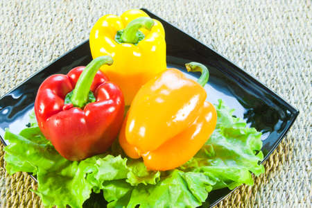 Bulgarian sweet pepper of red and yellow color and leaves of lettuce