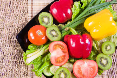 Varicoloured fruit and vegetables lie on a dish Stock Photo