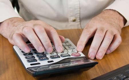 masculine hands working on a calculator