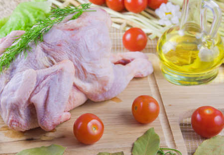 chicken carcass on a wooden board with tomatoes and fresh greenery Stock Photo - 16714586