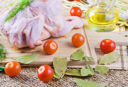 chicken carcass on a wooden board with tomatoes and fresh greenery Stock Photo - 16714606
