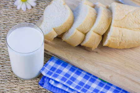 fresh cut long loaf and milk in a jug photo