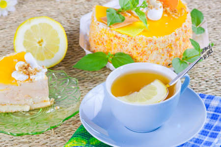 a delicious sweet cake is beautifully decorated and cup of tea with a lemon Stock Photo - 16714590