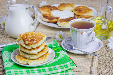 cup with tea, curd pancakes on a dish and milk photo