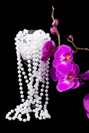 flowers of pink  orchid and beads from white pearls on a  black  background photo