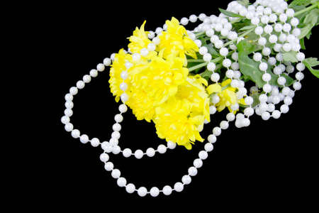 yellow chrysanthemums and beads are pearls on a black background photo