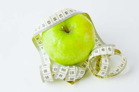 green apple and centimetre on a white background Stock Photo - 17278986