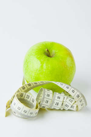 centimetre: green apple and centimetre on a white background