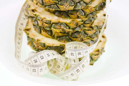 pineapple  and measuring ribbon on a white background Stock Photo - 17278990