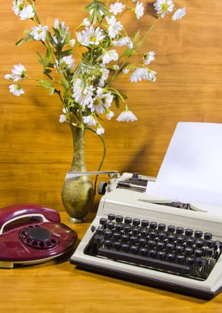 old typewriter, telephone and ancient vase with the bouquet of camomiles photo