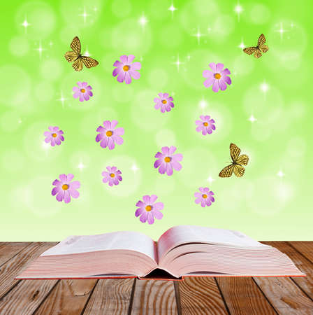 open book on a wooden surface with  flowers  and butterflies, collage photo