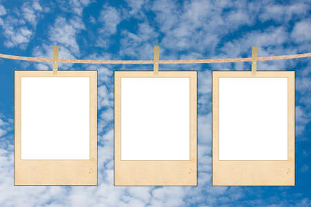 the clean white folias of paper hang on a rope on a background blue sky photo