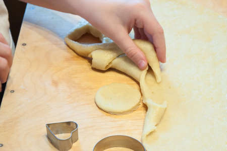 carves: The boy carves figures out of dough for biscuits Stock Photo