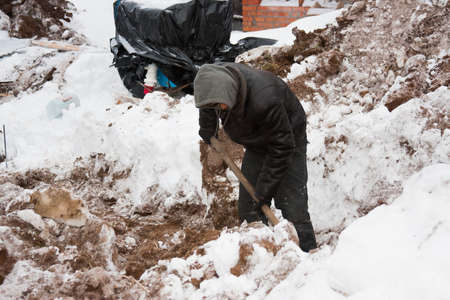 trench: PERM, RUSSIA, DECEMBER 15.2015: working with a shovel digging a trench for fence