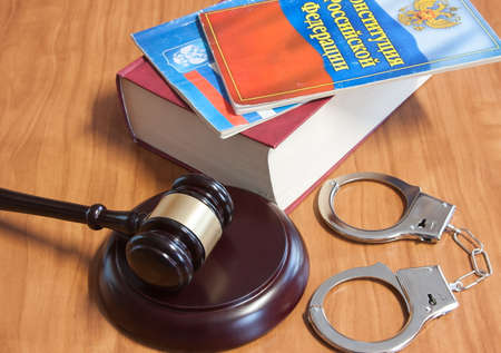 judicial: Judicial hammer, handcuffs and codes of laws on a wooden table