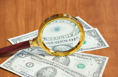 gilt: The magnifier in the gilt frame lays on dollars