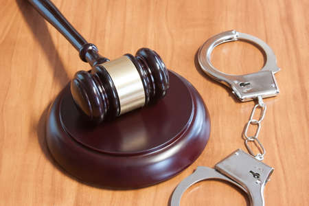judicial: Judicial hammer and handcuffs on a wooden table