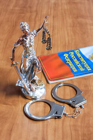 themis: A statuette of Themis, the constitution of the Russian Federation and the handcuffs on the table Stock Photo