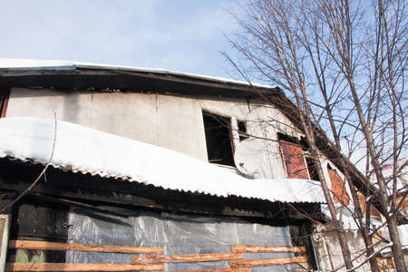 Abandoned house after fire on a background of blue sky