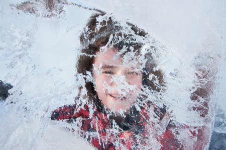 The boy looks through the ice sculpture, urban esplanade