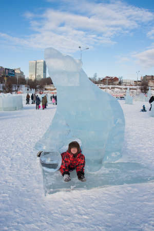 ice sculpture: PERM, RUSSIA, Feb, 06.2016: The boy in a bear ice sculpture, urban esplanade, Lenin Street Editorial