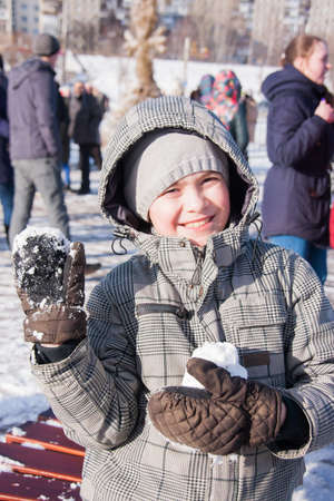 PERM, RUSSIA - March 13, 2016: Cheerful boy with snow in her hands, celebrating Shrovetide