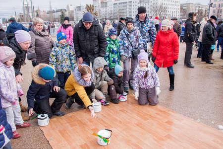 linoleum: PERM, RUSSIA - March 13, 2016: Children ride kettles on the linoleum, the celebration of Carnival