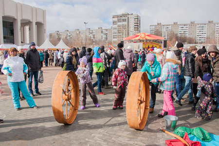 PERM, RUSSIA - March 13, 2016: Children ride the big wheel at the celebration of Carnival Editorial