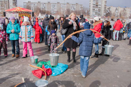 learns: PERM, RUSSIA - March 13, 2016: A boy learns to fetch water in the beam at the celebration of Carnival