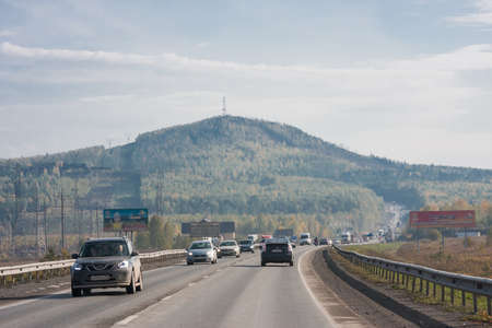 Perm, Russia - September 24.2016: Mountain in the distance and the road with cars Editorial