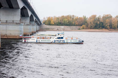 Perm, Russia - September 28,2016:  Walking boat leaves from under the bridge on the river Kama in the autumn evening