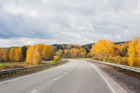 Revda, Russia -  Autumn landscape with road and the blue sky