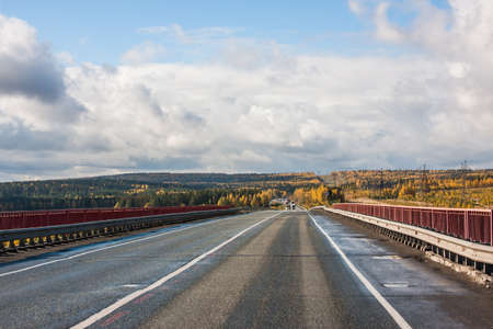 Revda, Russia - Autumn landscape with road, cars and beautiful blue sky