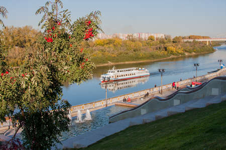 borne fontaine: Tyumen, Russia - October 01.2016:  Walking boat on the river, beautiful quay with fountains
