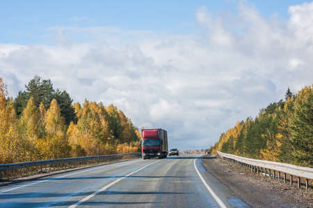 Revda, Russia - October 02.2016: Autumn landscape with road, cars and beautiful blue sky Editorial