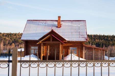 Wooden modern house behind a fence, Sverdlovsk Region, Russia