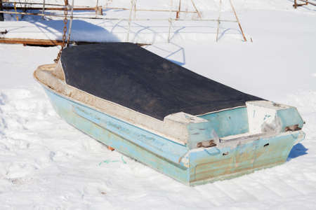 Boat without a motor car in winter day under a tent on snow