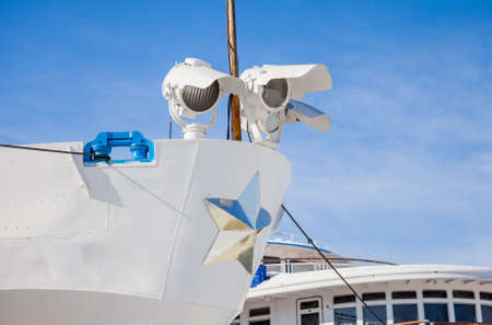 ship bow: Fragment of a three-deck motor ship with searchlights on a background of blue sky