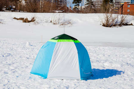 kama: Tent of the fisherman in the winter afternoon on the frozen river