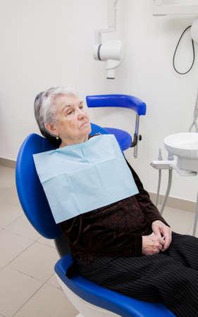 歯科クリニックで高齢者の女性は肘掛け椅子に座っています。 写真素材