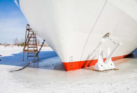 Fragment of a three-deck motor ship with an anchor in the ice in the backwaters of the river